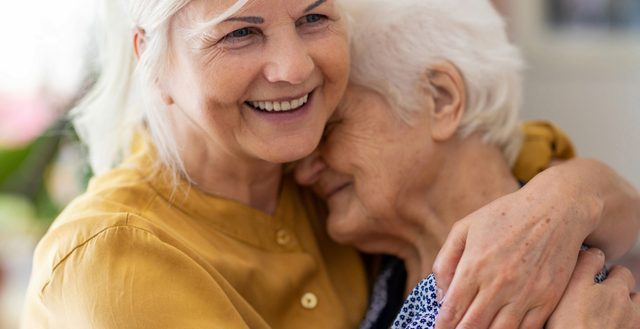 Family caregiver embracing the elderly parent