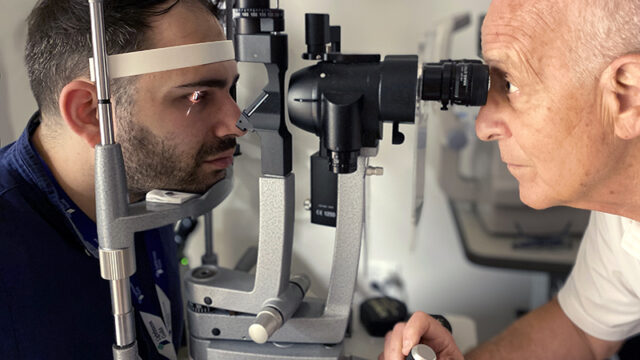 A young male client getting eye exam.