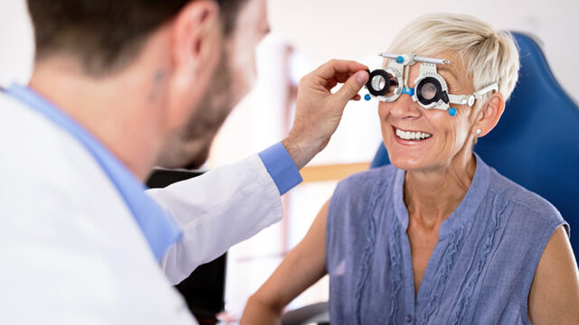 An optometrist selecting lenses for his client.