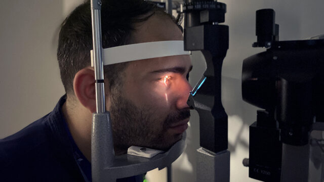 A young adult male patient having light shined into his eye during an eye exam.