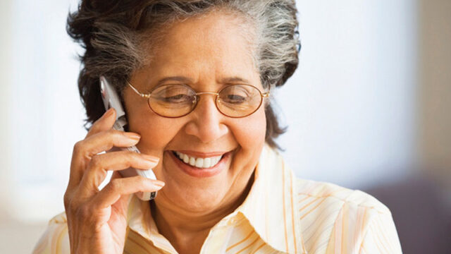A smiling elderly lady on the phone.