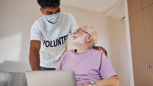 A young male volunteer with an elderly senior client.