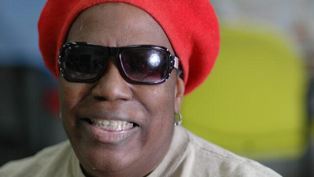 A smiling elderly lady wearing dark glasses.