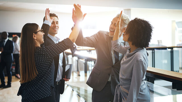 Happy professional people doing hi five in the office.